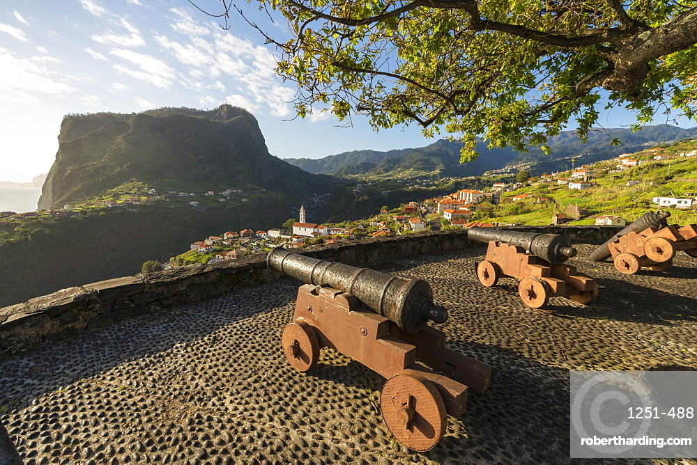 Historical cannons at Faial fortress with the village in the background. Faial, Santana municipality, Madeira region, Portugal.
