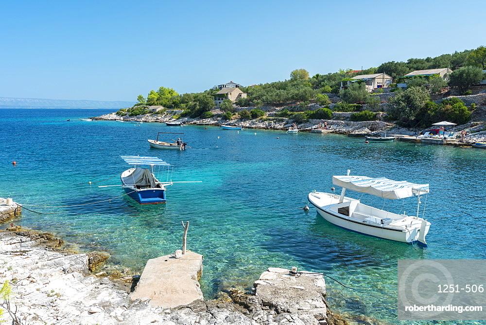 Boats at the little pier of Tankaraca cove in summer. Vela Luka, Korcula island, Dubrovnik - Neretva county, Croatia.