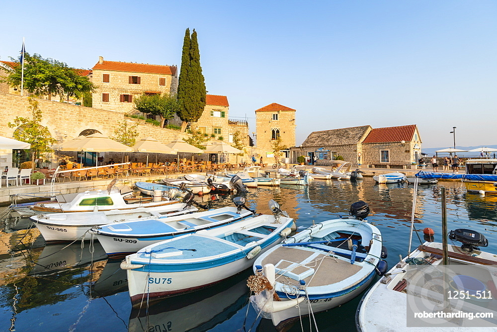 Boats at the pier of the town at sunset. Bol, Brac island, Split - Dalmatia county, Croatia.
