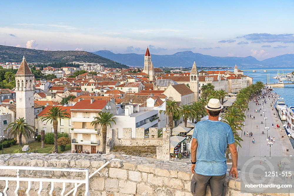 Man with hat admiring the old town from Karmelengo castle, in summer. Trogir, Split - Dalmatia county, Croatia.