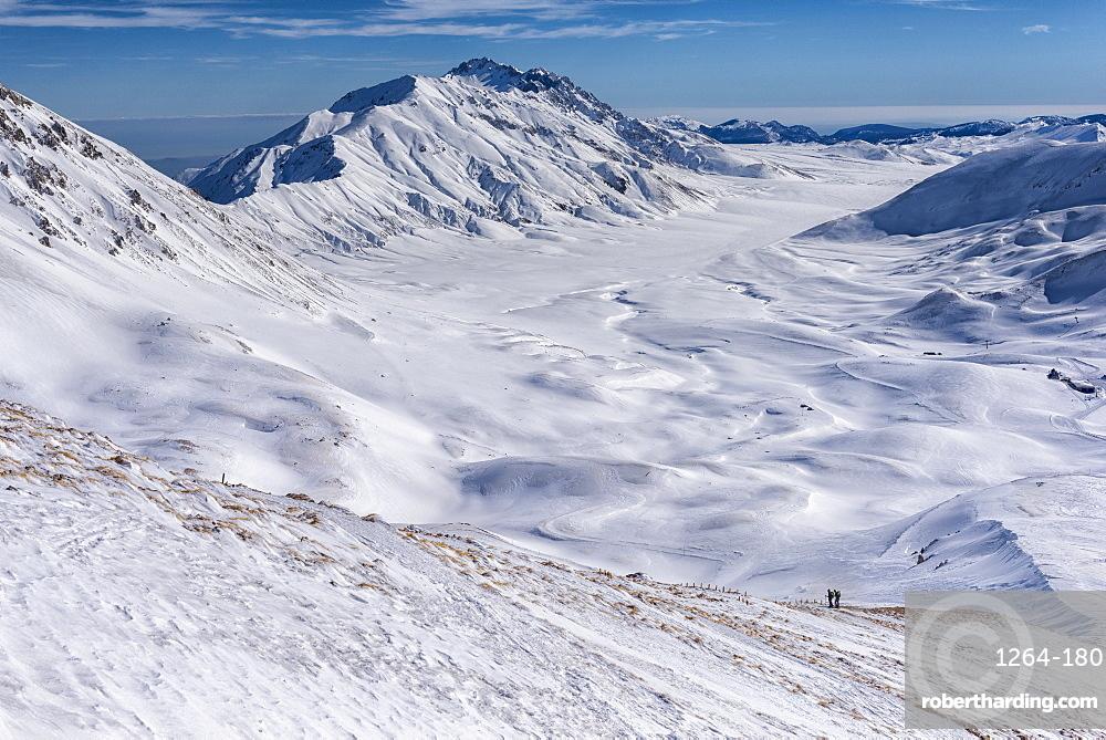 Italy, Abruzzo, Gran Sasso e Monti della Laga, Hikers on Campo Imperatore plateau in Winter