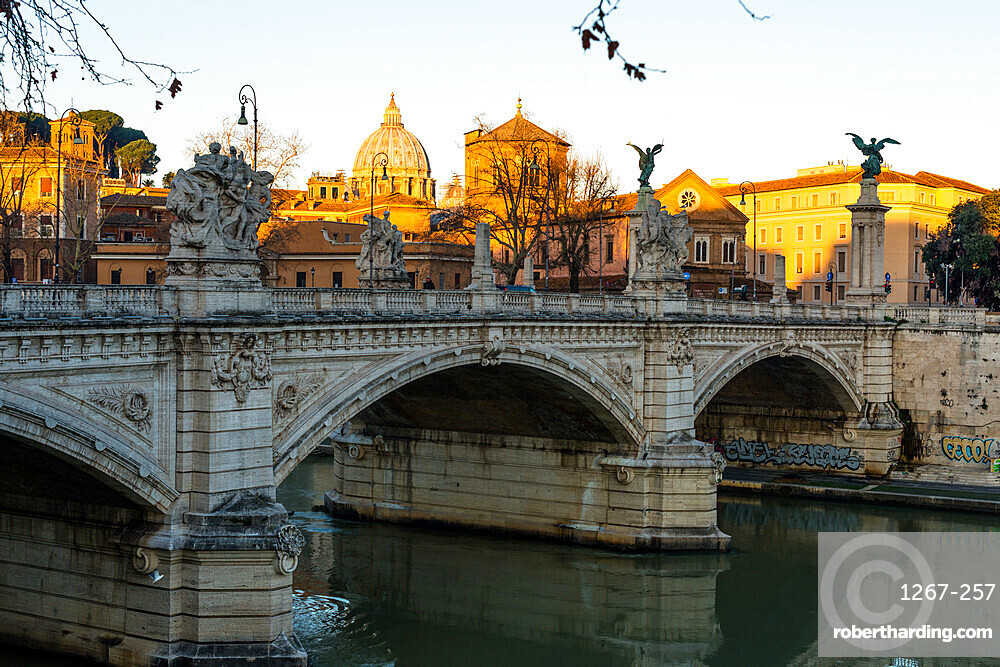 Sunrise hits the Vatican and St. Peter's Basilica but has not reached Vittorio Emanuele II bridge in the foreground, Rome, Lazio, Italy, Europe