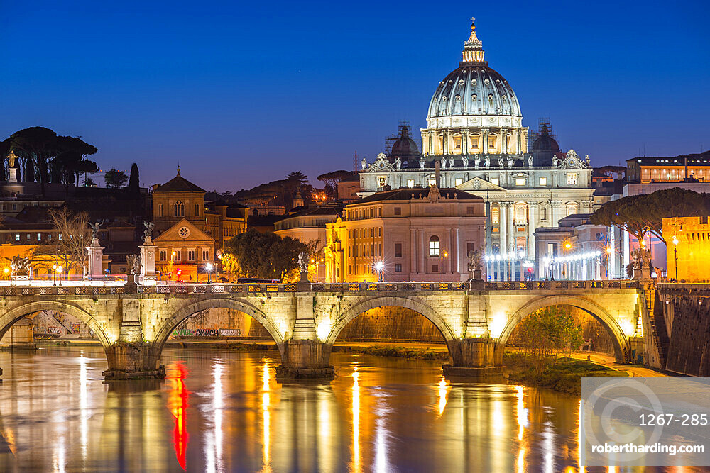 Illuminated St. Peters Basilica and the Vatican with Ponte St Angelo over the River Tiber at dusk, Rome, Lazio, Italy, Europe