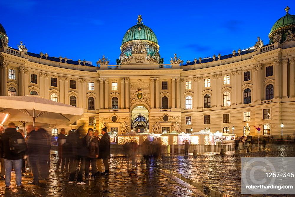 Christmas market on Michaelerplatz with Hofburg palace at dusk. Vienna, Austria.