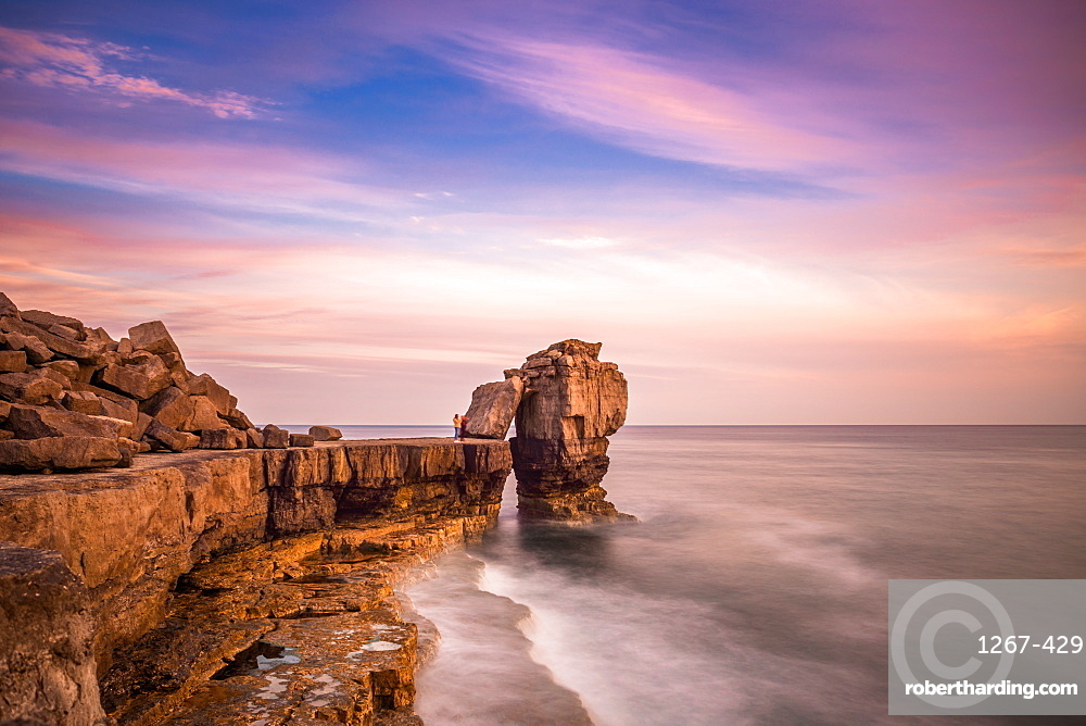 Sunset at Pulpit Rock, limestone sea stack on heavily quarried coast of Portland Bill in Dorset on England's Jurassic Coast. UK.