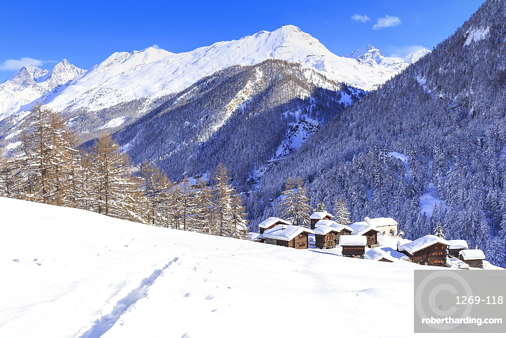 A trail in the snow leads to the traditional huts of Blatten, Zermatt, Canton of Valais (Wallis), Switzerland, Europe