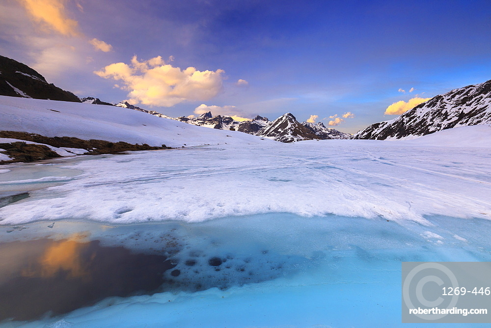 Sunset during thaw at the Malghera Lake, Valtellina, Lombardy, Italy, Europe
