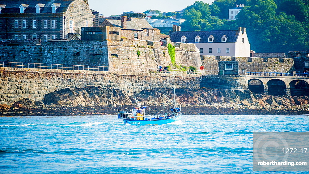 Traditional guernsey crab/lobster boat coming into St. Peter Port Harbour, passing Castle Cornet
