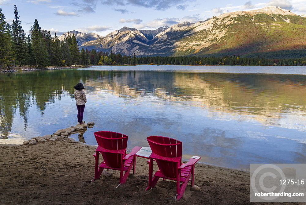 Tourist and the Red Chairs in the Lake Edith, Jasper National Park, Alberta, Canada