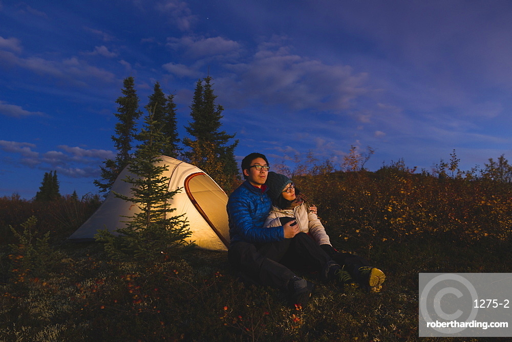 Couple sitting in front of an illuminated tent, Alaska, United States of America, North America