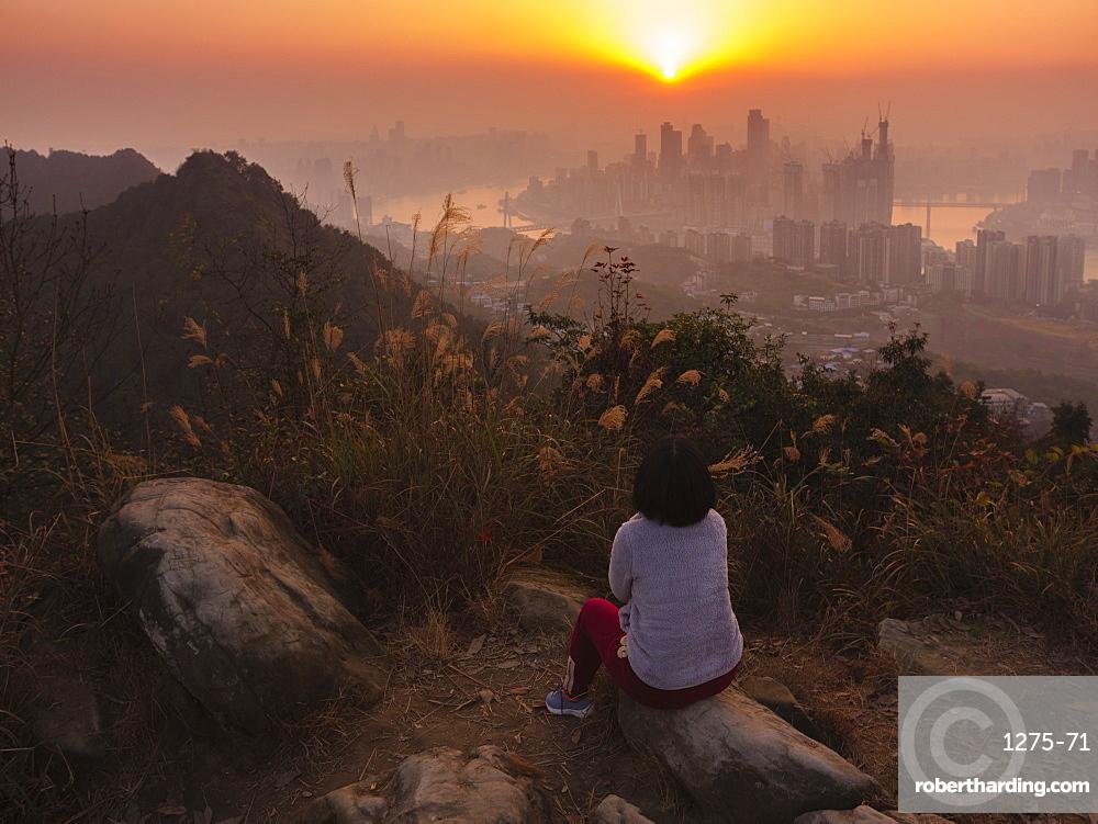 Tourist enjoys watching sunset of Chongqing skyline from the Nanshan mountain