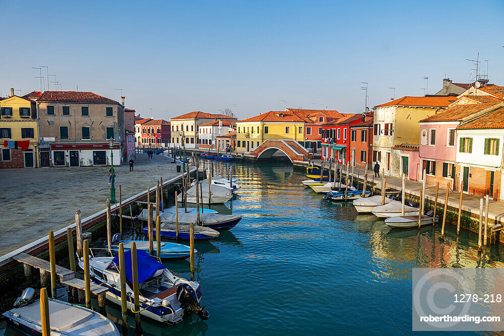 Murano, Italy view of Ponte San Martino stone bridge over canal with colorful buildings & moored boats on wooden wharf pilings.