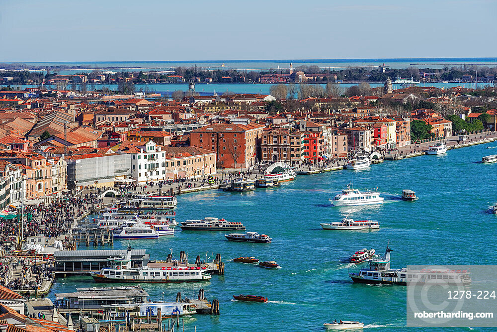 Venice Italy panoramic day view of waterfront with boats & low rise buildings with red tiles, seen from Saint Marks Campanile.