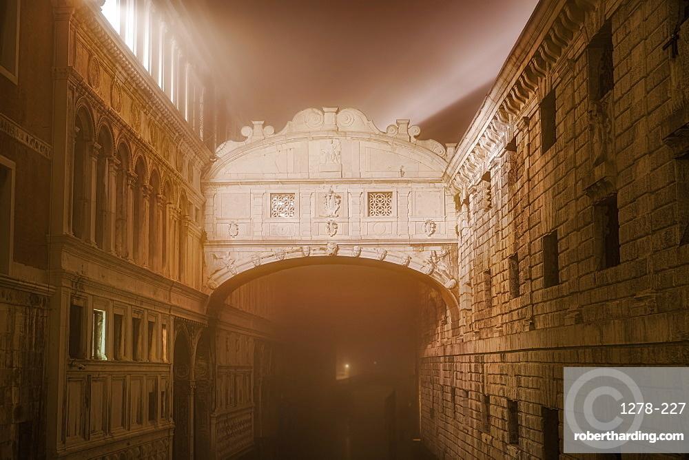 Venice, Italy foggy view without crowd of Ponte de Sospiri, iconic Bridge of Sighs stone bridge at night.