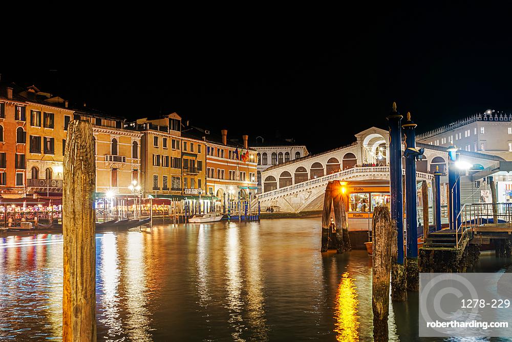 Venice Italy night view of illuminated Ponte di Rialto, Rialto pedestrian stone arch Bridge & traditional Grand Canal buildings.