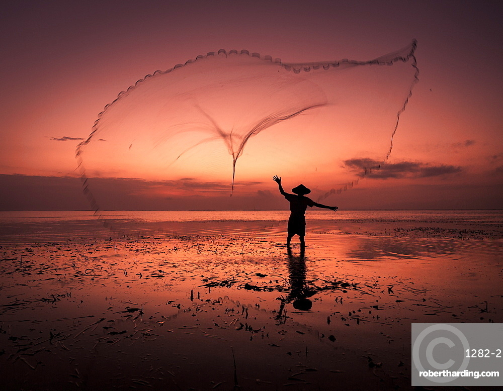 Sunrise fisherman casting his net, Bali, Indonesia, South East Asia.