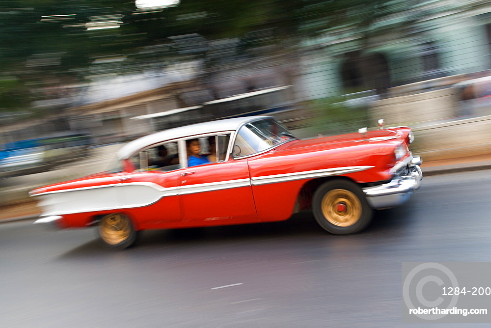Old vintage American red and white car driving along a street in Havana, Cuba, West Indies, Caribbean, Central America
