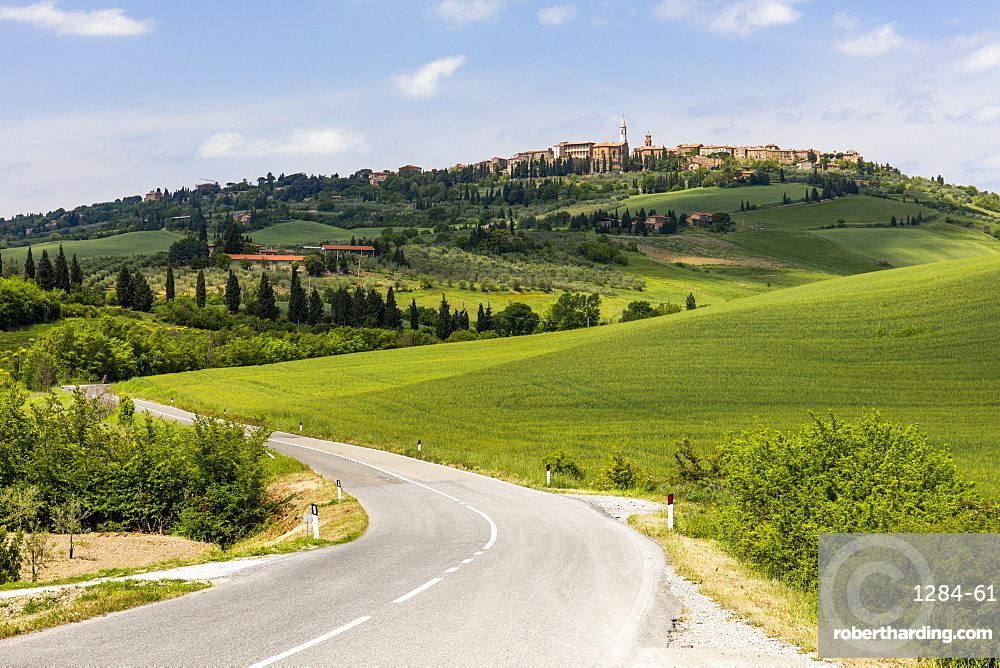 Tuscan road winding through green fields towards Pienza, Tuscany, Italy, Europe