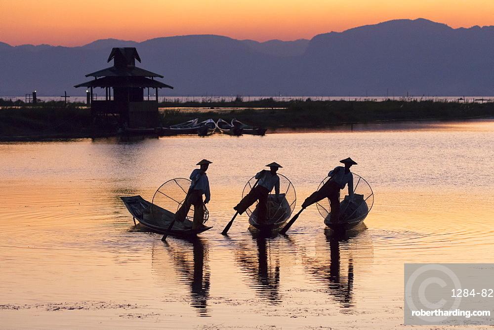 Three fishermen balance on one leg at sunset on Inle Lake, Shan State, Myanmar (Burma), Asia