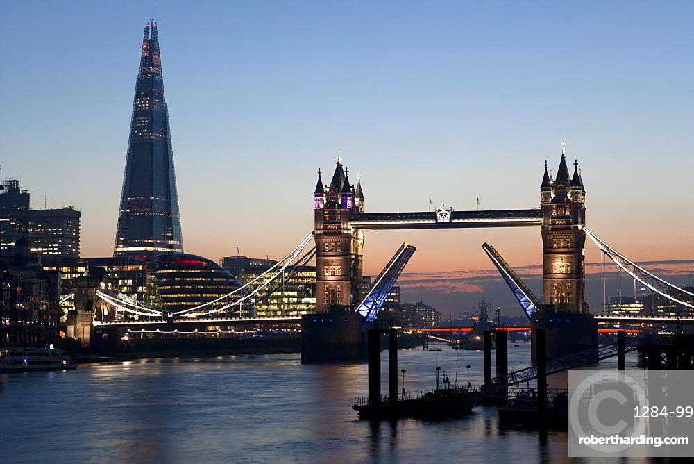 Tower Bridge illuminated at night, with the bridge raised over the River Thames, London, England, United Kingdom, Europe