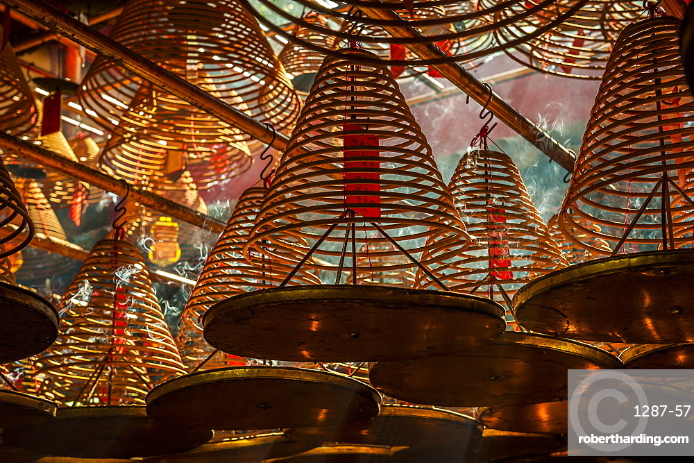 Beams of light streaming into Man Mo Temple past the large incense coils hanging from the ceiling of the Temple, Hong Kong, China, Asia