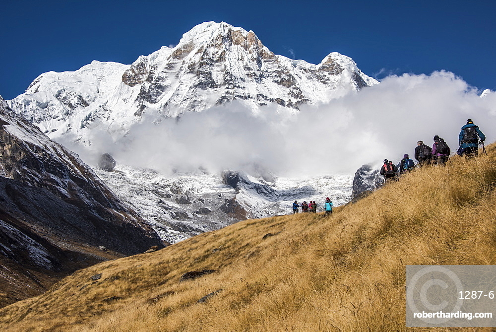 A group of Trekkers approaching Annapurna Base Camp, with Annapurna South looming large in the background