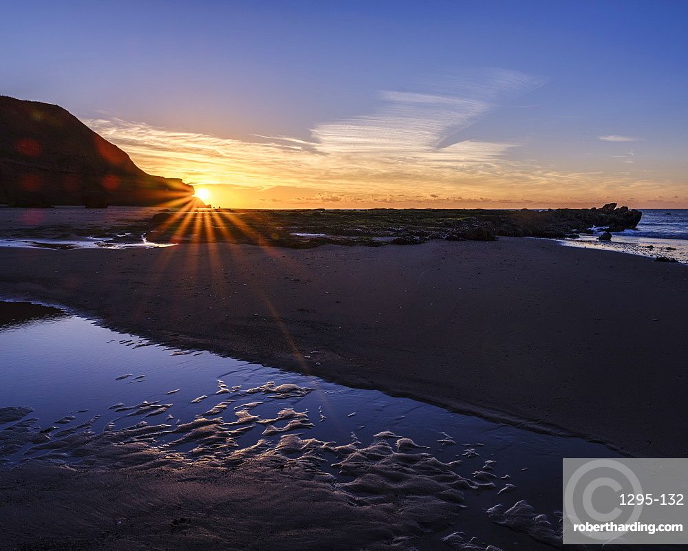 Sunstar peeping around the cliffs with a pool on the beach at Orcombe Point, Exmouth, Devon, UK.