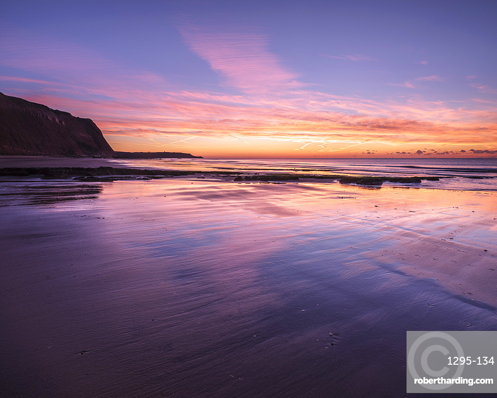 Dawn twilight with clouds reflected on the wet beach at Orcombe Point and Sandy Bay, Exmouth, Devon, UK.