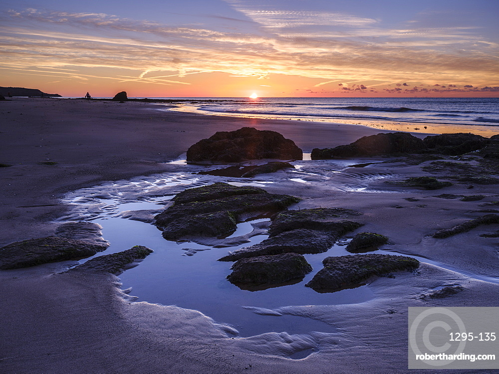 Sunrise on the shoreline with rocks and rock pools at Orcombe Point, Exmouth, Devon, UK.