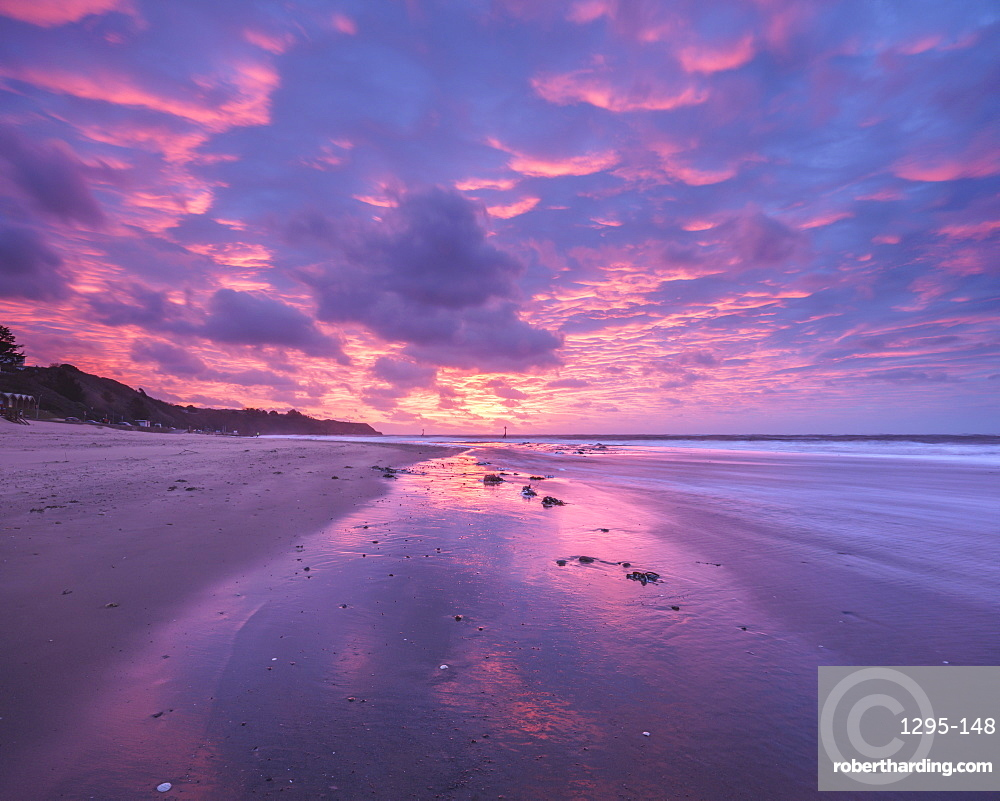 Intensely coloured and mirrored dawn sky looking towards Orcombe Point, Exmouth, Devon, UK