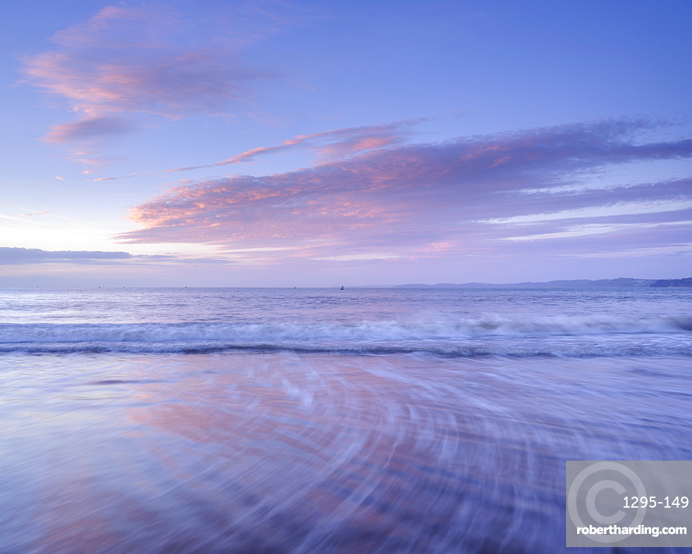 Tranquil dawn with clouds reflected in the wet beach, Exmouth, Devon, UK