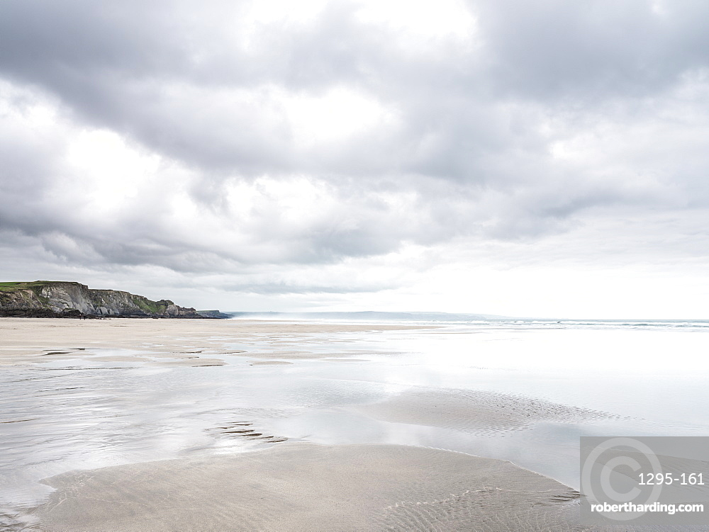 Cloud formations and wet sand on the vast expanse of beach at Sandymouth, looking towards Bude, Cornwall, UK