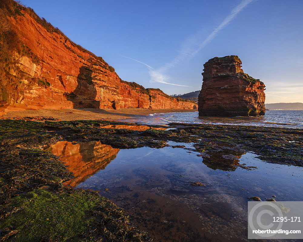 Dawn on the beach with one of the majestic sea stacks at Ladram Bay, Sidmouth, Devon, UK