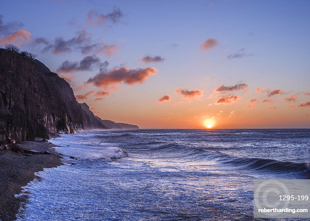 Stormy seas at sunrise at the cliffs in the seaside town of Sidmouth, Devon, UK