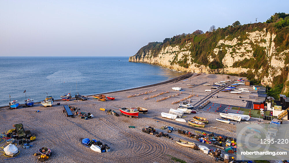 Fishing boats and deckchairs on the popular pebbled beach at Beer near Seaton, Devon, UK