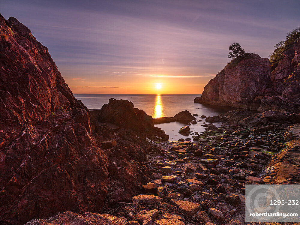 A colourful sunrise over Torbay with warm light on rocks, Babbacombe, Torquay, Devon, UK