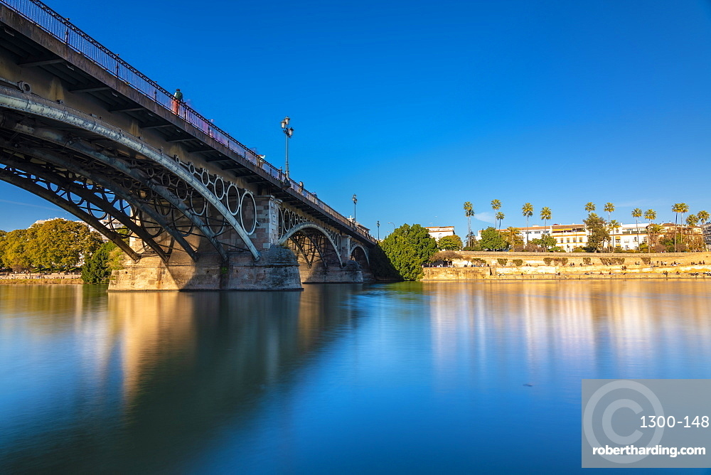 Long exposure of Puente de Triana on Guadalquivir River with Seville in the background
