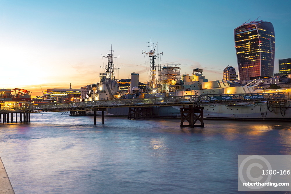 Skyline of city of London at sunset with Hms Belfast in the foreground
