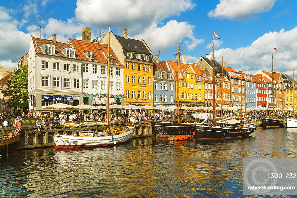 Nyhavn in Kopenhagen with old colorful andhousesboats anchored in summer