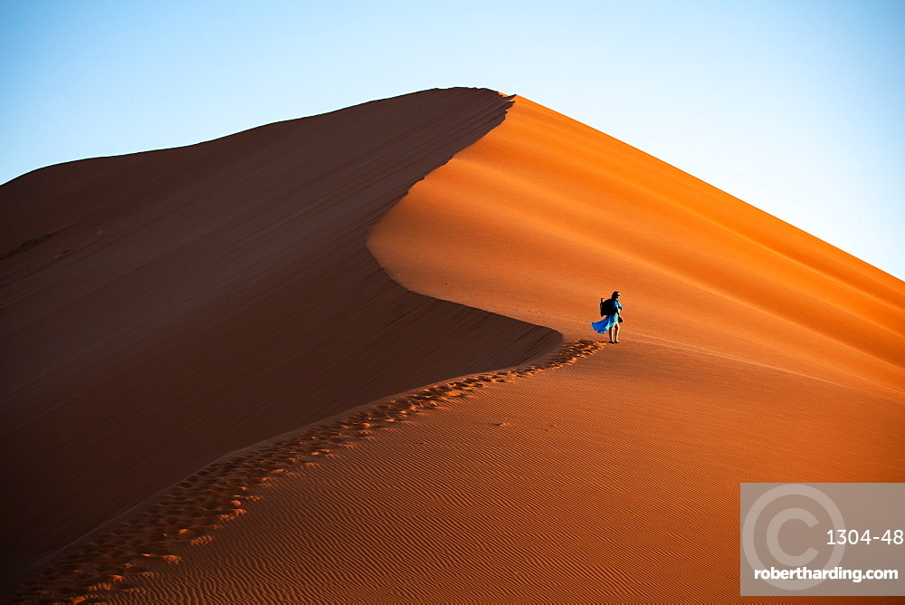 Shot of model Climbing Dune 13 with photography gear, Sossusvlei, Namibia, Africa