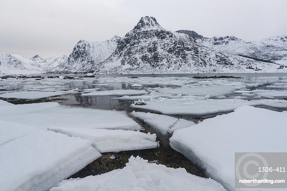Cracked ice and snow covered mountains, Lofoten Islands, Nordland, Norway.