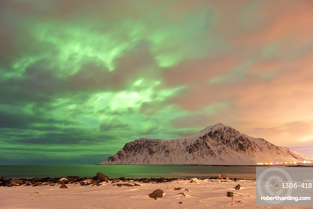 The Northern Lights with mountain range in winter, Reine, Lofoten Islands, Norway.