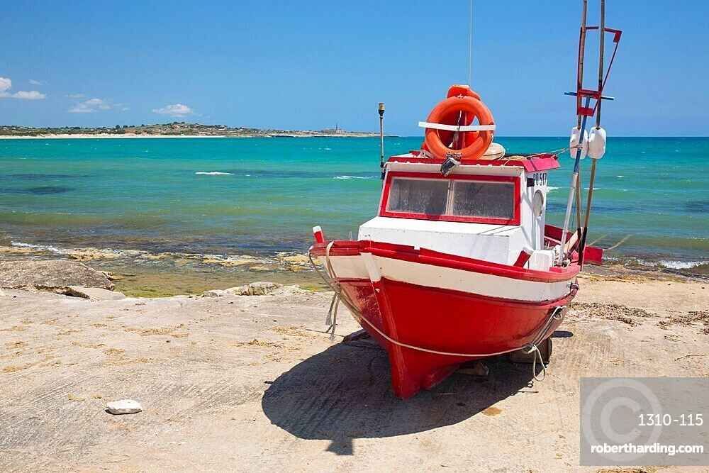 Colourful fishing boat on slipway, the turquoise waters of the Mediterranean Sea beyond, Sampieri, Ragusa, Sicily, Italy