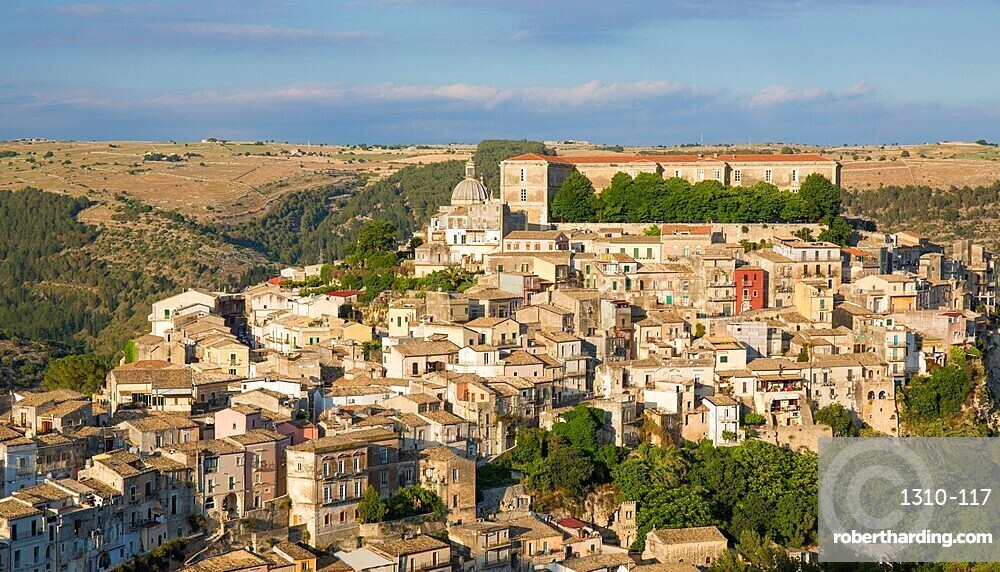View over the sunlit rooftops of Ragusa Ibla, evening, houses clinging to steep hillside, Ragusa, Sicily, Italy