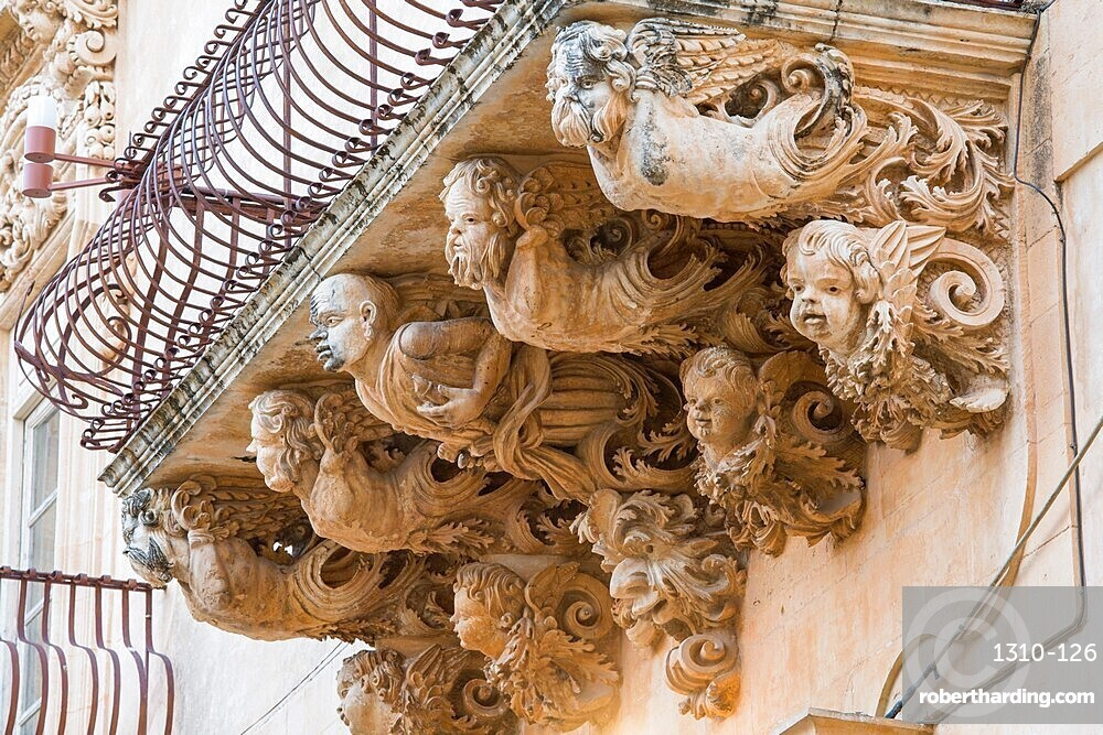 Grotesque figures supporting balcony on the baroque Palazzo Nicolaci di Villadorata, Noto, Syracuse, aka Siracusa, Sicily, Italy