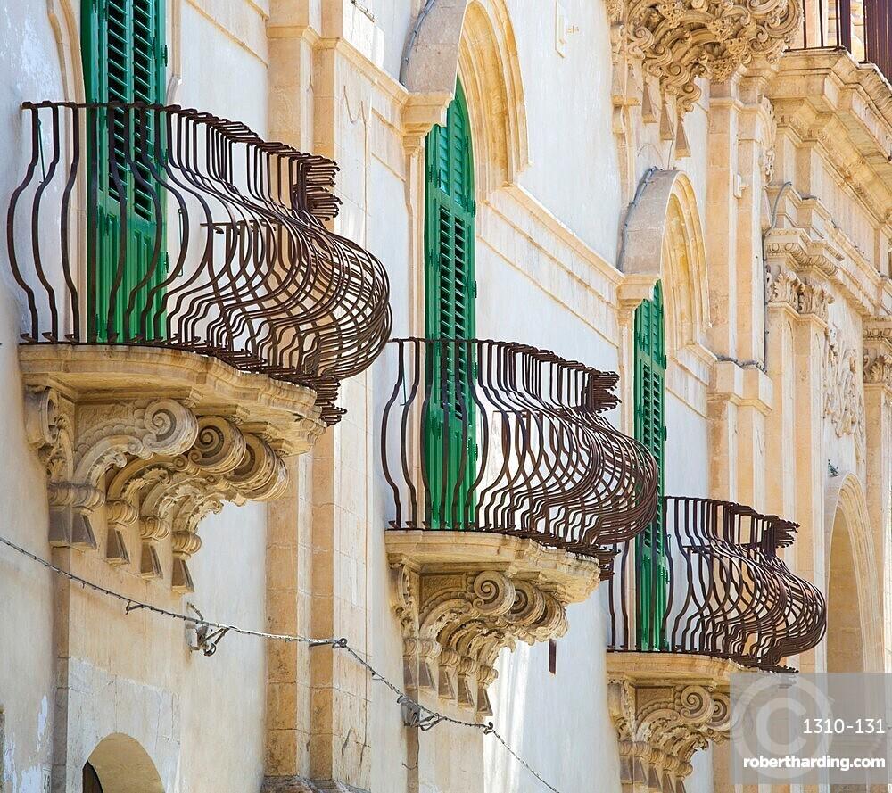 Typical wrought iron balconies on the baroque Palazzo Astuto di Fargione, Noto, Syracuse, aka Siracusa, Sicily, Italy