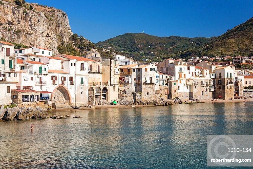 View across harbour to the Old Town, houses clustered together along waterfront, Cefalu, Palermo, Sicily, Italy