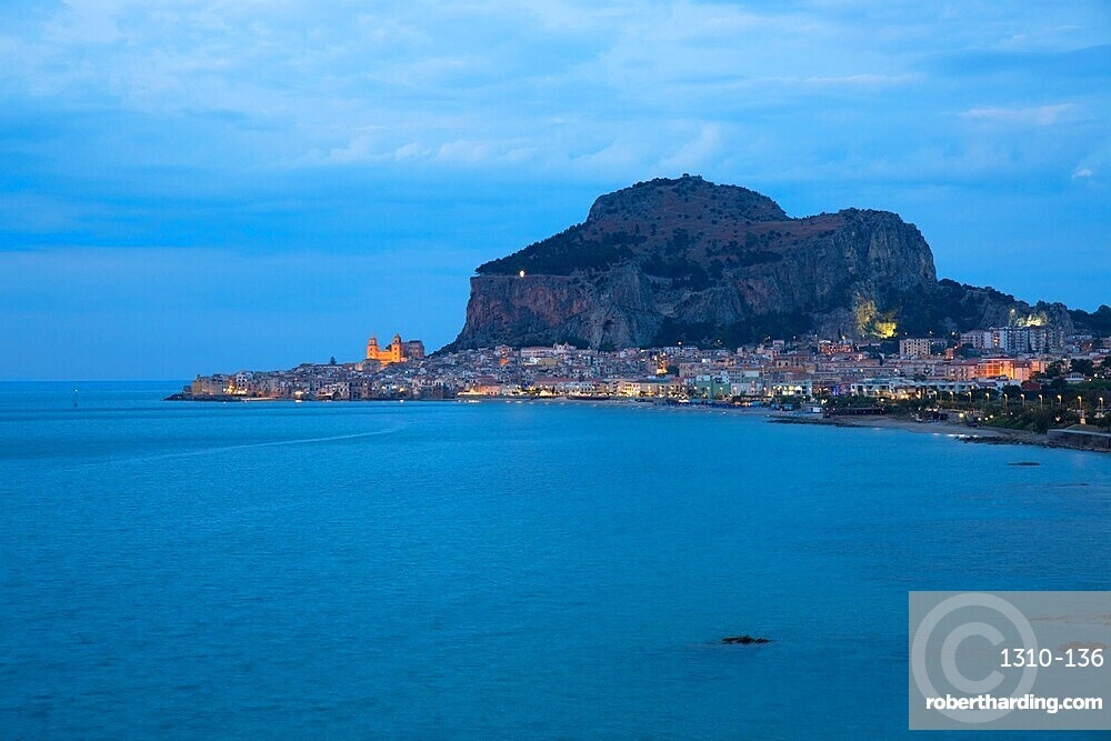 View along coast to the town and illuminated cathedral, dusk, La Rocca towering above, Cefalu, Palermo, Sicily, Italy