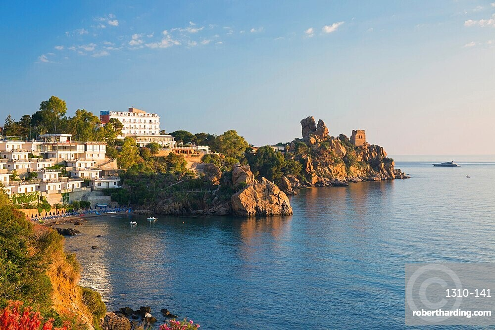 View across the tranquil waters of Calura Bay, sunrise, ancient watchtower visible on headland, Cefalu, Palermo, Sicily, Italy