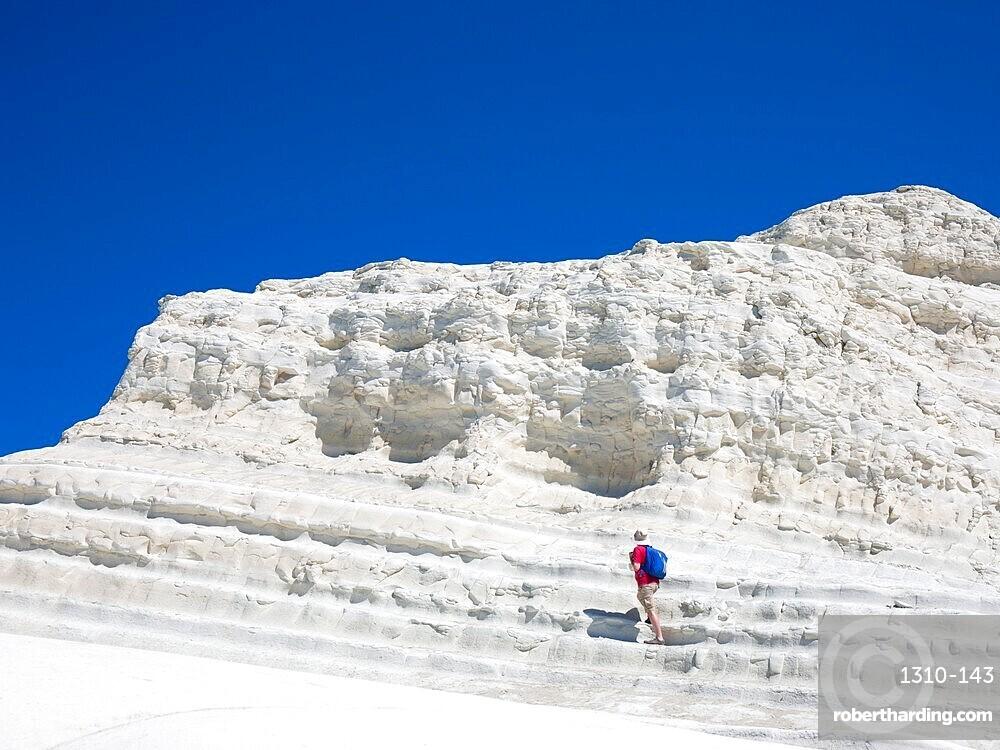 Visitor ascending the white limestone cliffs of the Scala dei Turchi, Realmonte, Porto Empedocle, Agrigento, Sicily, Italy